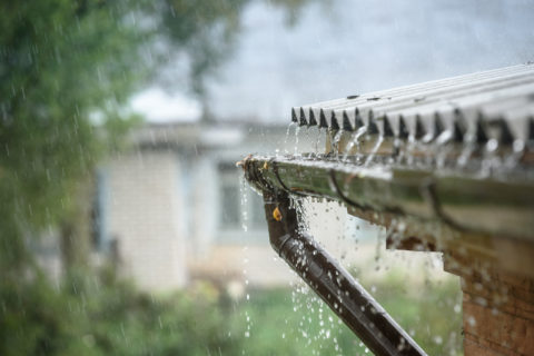 Heavy rain falling into gutters on home